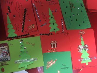 Bevers delen kerstkaarten en kerstkransjes uit